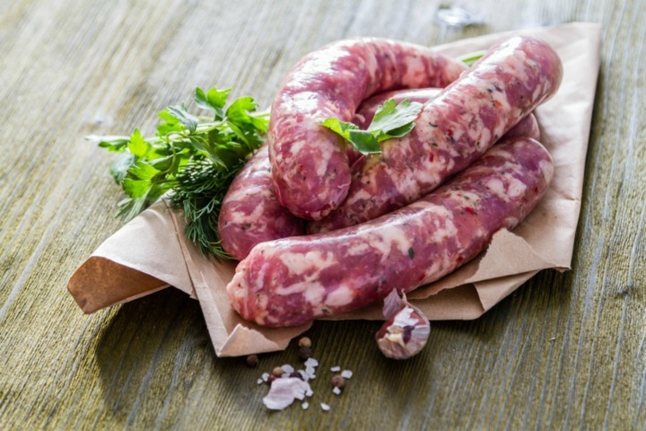 Raw sausages  with herbs and spices, wood background